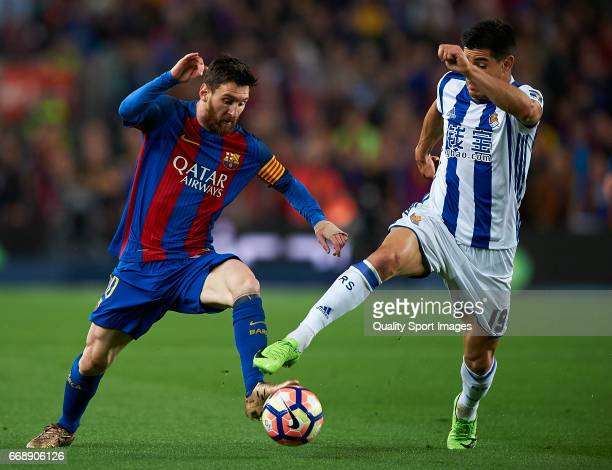 Lionel Messi of Barcelona competes for the ball with Yuri Berchiche Izeta of Real Sociedad during the La Liga match between FC Barcelona and Real...