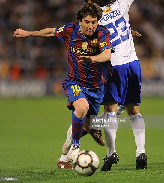 Lionel Messi of Barcelona dribbles the ball past Leonardo Ponzio of Real Zaragoza during the La Liga match between Real Zaragoza and Barcelona at La...
