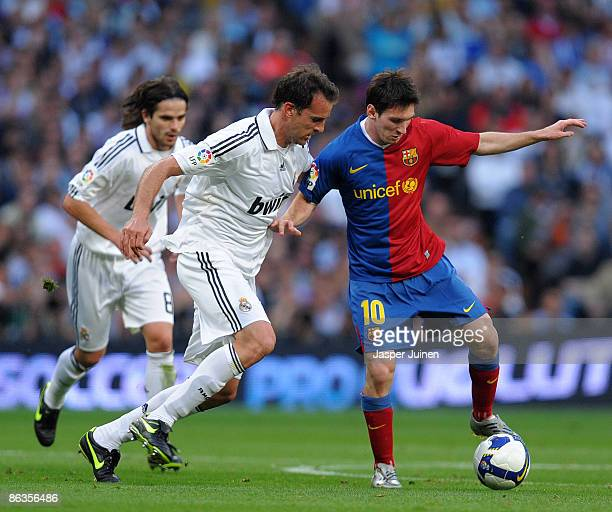 Lionel Messi of Barcelona duels for the ball with Christoph Metzelder of Real Madrid during the La Liga match between Real Madrid and Barcelona at...