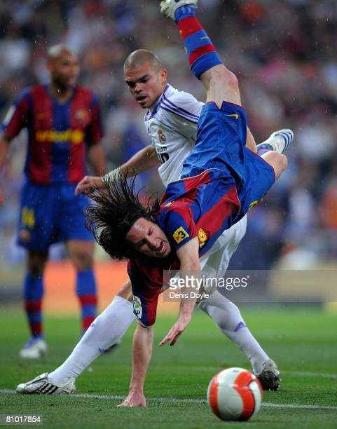 Lionel Messi of Barcelona falls over Pepe of Real Madrid during the La Liga match between Real Madrid and Barcelona at the Santiago Bernabeu stadium...