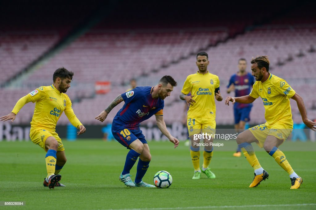 Lionel Messi of Barcelona figths for the ball with Alberto Aquilani and Tana of Las Palmas during the La Liga match between Barcelona and Las Palmas at Camp Nou on October 1, 2017 in Barcelona, Spain.