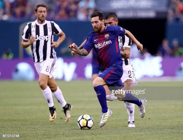 Lionel Messi of Barcelona heads for the goal as Stefano Sturaro and Claudio Marchisio of Juventus defend in the first half during the International...
