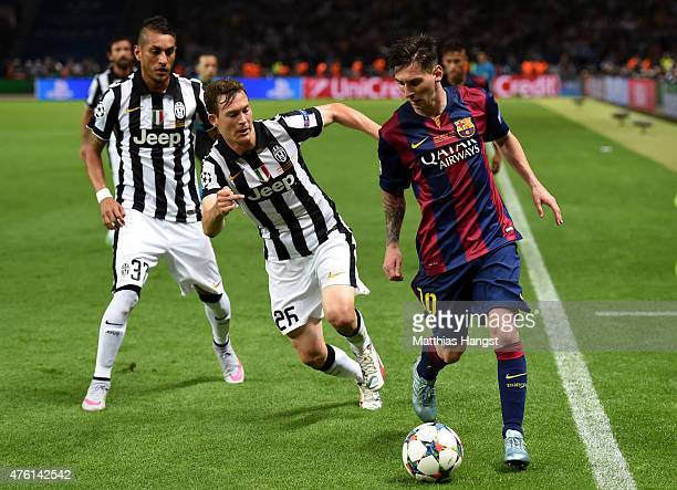 Lionel Messi of Barcelona holds off Stephan Lichtsteiner of Juventus during the UEFA Champions League Final between Juventus and FC Barcelona at...