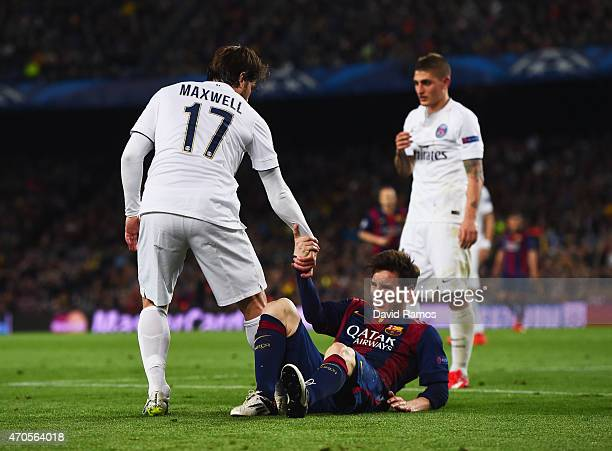Lionel Messi of Barcelona is assisted by Maxwell of PSG during the UEFA Champions League Quarter Final second leg match between FC Barcelona and...
