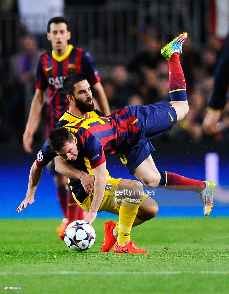Lionel Messi of Barcelona is challenged by Arda Turan of Club Atletico de Madrid during the UEFA Champions League Quarter Final first leg match between FC Barcelona and Club Atletico de Madrid at Camp Nou on April 1, 2014 in Barcelona, Spain.