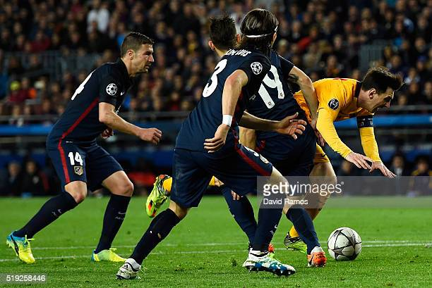 Lionel Messi of Barcelona is challenged by Lucas Hernandez of Atletico Madrid during the UEFA Champions League quarter final first leg match between...