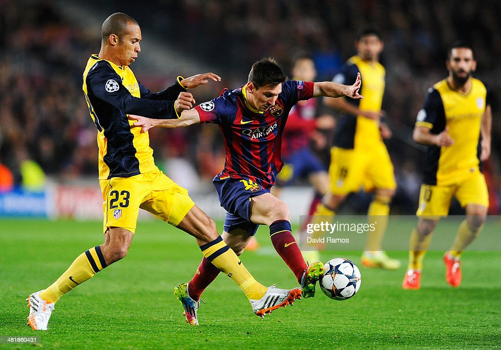 Lionel Messi of Barcelona is challenged by Miranda of Club Atletico de Madrid during the UEFA Champions League Quarter Final first leg match between FC Barcelona and Club Atletico de Madrid at Camp Nou on April 1, 2014 in Barcelona, Spain.