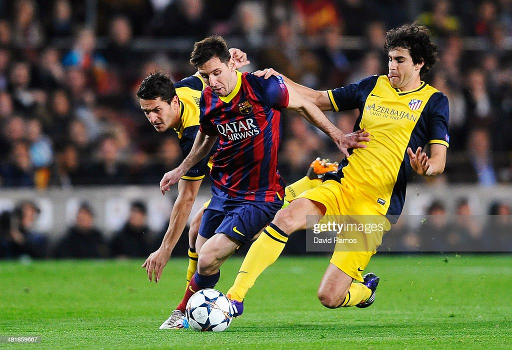 Lionel Messi of Barcelona is challenged by Tiago (R) and Koke of Club Atletico de Madrid during the UEFA Champions League Quarter Final first leg match between FC Barcelona and Club Atletico de Madrid at Camp Nou on April 1, 2014 in Barcelona, Spain.