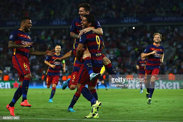 Lionel Messi of Barcelona is congratulated by Luis Suarez after scoring his second goal by team mates during the UEFA Super Cup between Barcelona and...