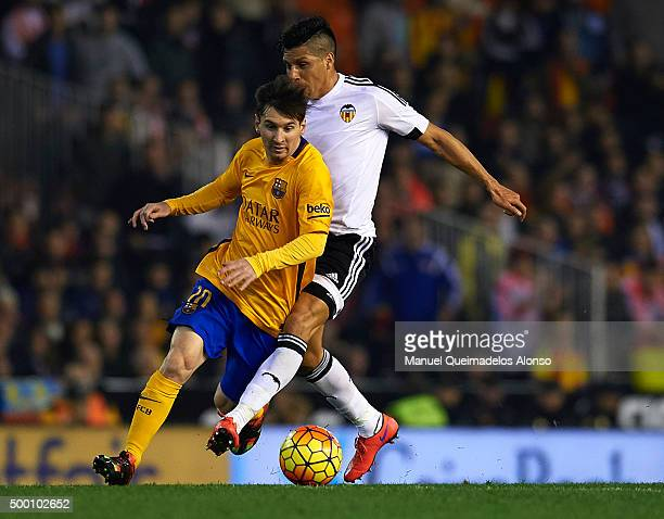 Lionel Messi of Barcelona is tackled by Enzo Perez of Valencia during the La Liga match between Valencia CF and FC Barcelona at Estadi de Mestalla on...