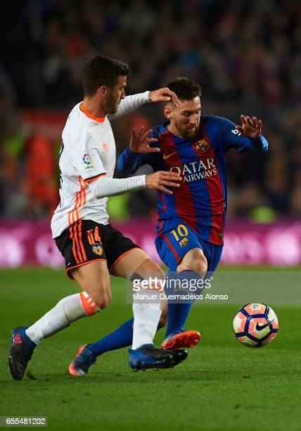 Lionel Messi of Barcelona is tackled by Jose Luis Gaya of Valencia during the La Liga match between FC Barcelona and Valencia CF at Camp Nou Stadium...