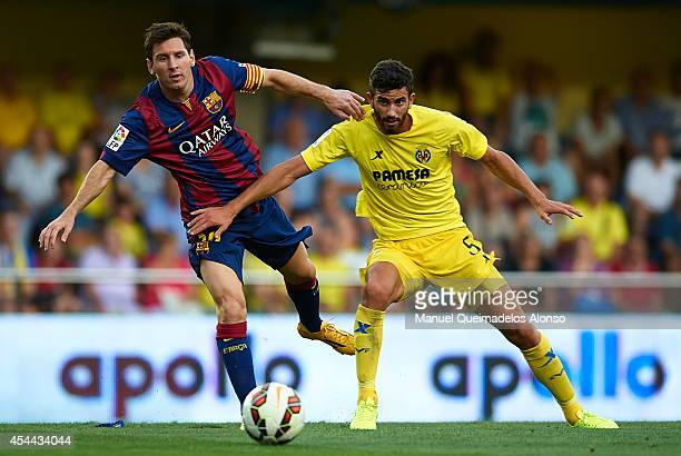 Lionel Messi of Barcelona is tackled by Mateo Pablo Musacchio of Villarreal during the La Liga match between Villarreal CF and FC Barcelona at El...