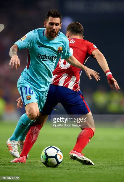 Lionel Messi of Barcelona is tackled by Saul Niguez of Atletico de Madrid during the La Liga match between Atletico Madrid and Barcelona at Estadio...