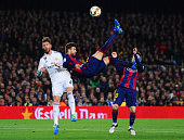 Lionel Messi of Barcelona looks on as Gerard Pique of Barcelona attempts an overhead kick under challenge from Sergio Ramos of Real Madrid CF during...