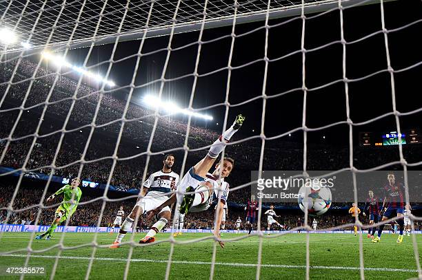 Lionel Messi of Barcelona scores his team's second goal despite the efforts from Rafinha of Bayern Muenchen during the UEFA Champions League Semi...