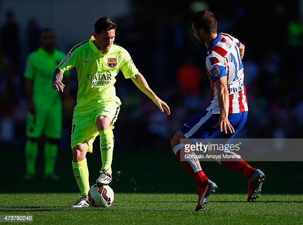 Lionel Messi of Barcelona takes on Gabi of Atletico Madrid during the La Liga match between Club Atletico de Madrid and FC Barcelona at Vicente...