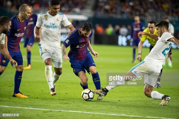 Lionel Messi of Barcelona weaves through Marco Asensio of Real Madrid and Casemiro of Real Madrid during the International Champions Cup El Clásico...