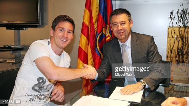 Lionel Messi of FC Barcelona and the FC Barcelona President Josep Maria Bartomeu shake hands following the signing of his new contract with FC...