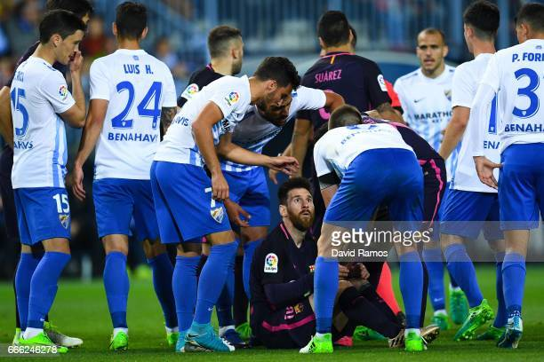 Lionel Messi of FC Barcelona argues with Malaga players after being brought down during the La Liga match between Malaga CF and FC Barcelona at La...