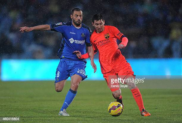 Lionel Messi of FC Barcelona battles for the ball against Medhi Lacen of Getafe CF during the La Liga match between Getafe CF and FC Barcelona at the...