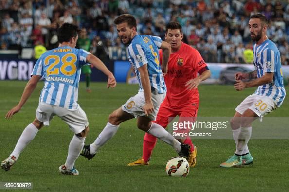 Lionel Messi of FC Barcelona beats Ignacio Camacho of Malaga CF during the La Liga match between Malaga CF and FC Barcelona at La Rosaleda studium on...
