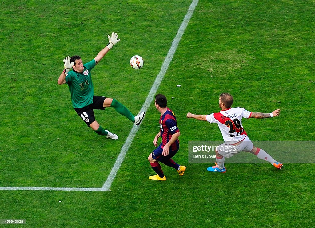 Lionel Messi (L) of FC Barcelona beats Tono Rodriguez of Rayo Vallecano de Madrid to score his team's opening goal during the La Liga match between Rayo Vallecano de Madrid and FC Barcelona at Estadio Teresa Rivero on October 4, 2014 in Madrid, Spain.