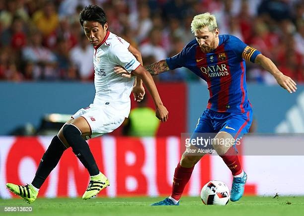Lionel Messi of FC Barcelona being followed by Hiroshi Kiyotake of Sevilla FC during the match between Sevilla FC vs FC Barcelona as part of the...
