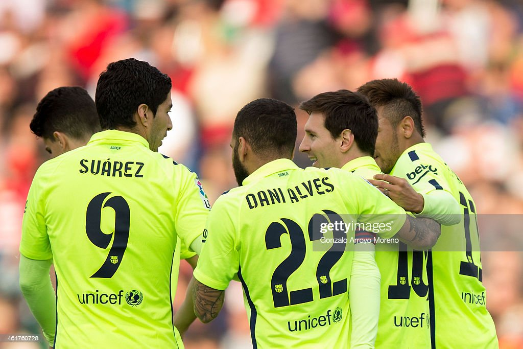 Lionel Messi of FC Barcelona celebrates scoring their third goal with teammatea Neymar JR Dani Alves and Luis Suarez during the La Liga match between...