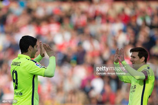 Lionel Messi of FC Barcelona celebrates scoring their third goal with teammate Luis Suarez during the La Liga match between Granada CF and FC...