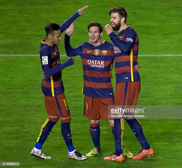 Lionel Messi of FC Barcelona celebrates scoring their third goal with teammates Neymar JR and Gerard Pique during the La Liga match between Rayo...