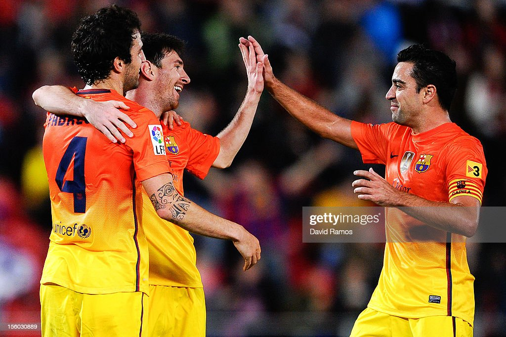 Lionel Messi of FC Barcelona (C) celebrates with Cesc Fabregas (L) and Xavi Hernandez of FC Barcelona after scoring his team's second goal during the La Liga match between RCD Mallorca and FC Barcelona at Iberostar Stadium on November 11, 2012 in Mallorca, Spain.