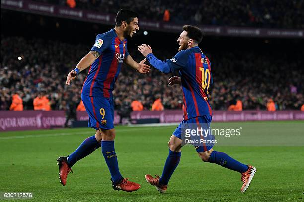 Lionel Messi of FC Barcelona celebrates with his team mate Luis Suarez after scoring his team's fourth goal during the La Liga match between FC...
