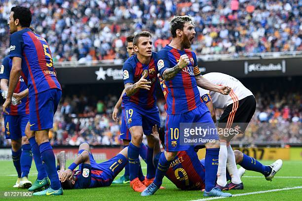 Lionel Messi of FC Barcelona celebrates with his team mates as Neymar Jr and Luis Suarez reacts on the pitch after being hit by objects thrown from...