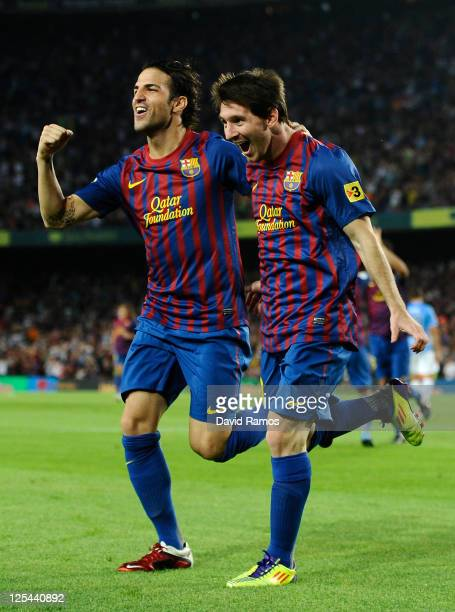 Lionel Messi of FC Barcelona celebrates with his teammate Cesc Fabregas after scoring his first goal during the La Liga soccer match between FC...