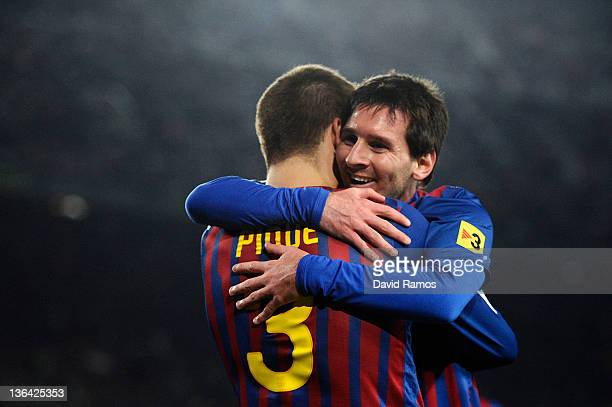 Lionel Messi of FC Barcelona celebrates with his teammate Gerard Pique of FC Barcelona after scoring his team's third goal during the round of last...