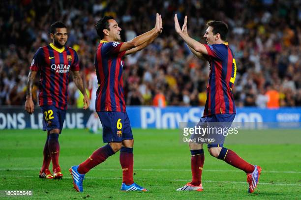 Lionel Messi of FC Barcelona celebrates with his teammate Xavi Hernandez after scoring his team's fourth goal during the UEFA Champions League Group...