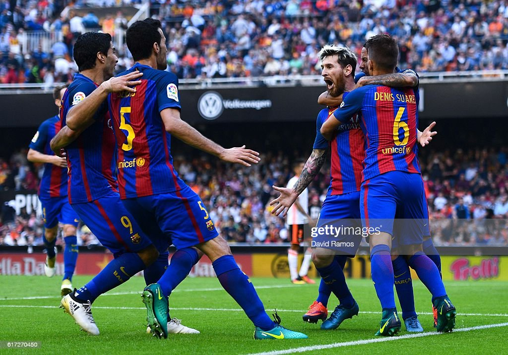 Lionel Messi (2ndR) of FC Barcelona celebrates with his teammates after scoring his team's third goal from the penalty spot during the La Liga match between Valencia CF and FC Barcelona at Mestalla stadium on October 22, 2016 in Valencia, Spain.
