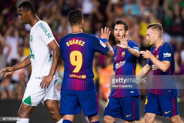 Lionel Messi of FC Barcelona celebrates with his teammates Luis Suarez and Gerard Deulofeu after scoring his team's third goal during the Joan Gamper...