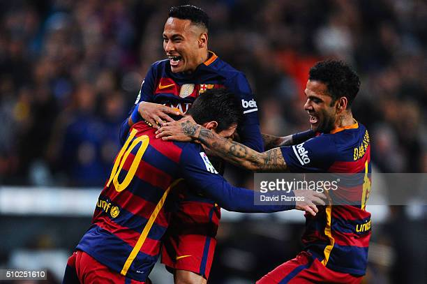 Lionel Messi of FC Barcelona celebrates with his teammates Neymar and Dani Alves of FC Barcelona after scoring the opening goal during the La Liga...