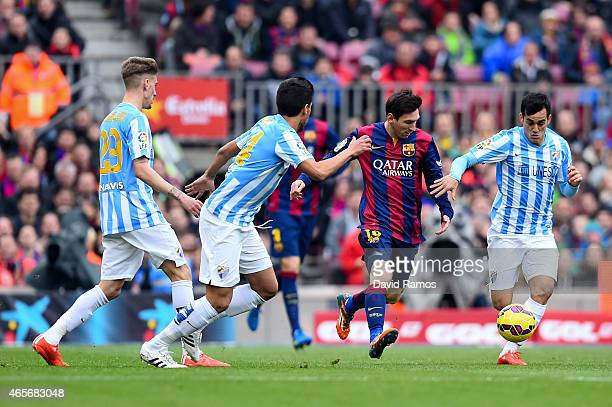 Lionel Messi of FC Barcelona competes for the ball against Malaga CF players during the La Liga match between FC Barcelona and Malaga CF at Camp Nou...