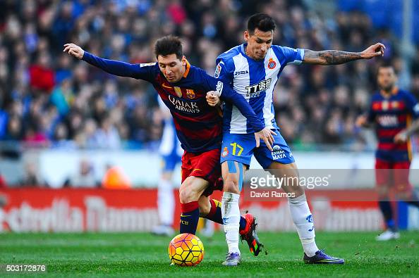 Lionel Messi of FC Barcelona competes for the ball Hernan Perez of RCD Espanyol during the La Liga match between RCD Espanyol and FC Barcelona at...