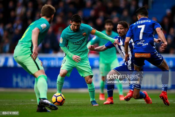 Lionel Messi of FC Barcelona competes for the ball with Alexis Ruano of Deportivo Alaves during the La Liga match between Deportivo Alaves and FC...