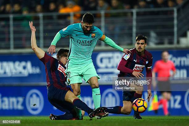 Lionel Messi of FC Barcelona competes for the ball with Ander Capa and Dani Garcia of SD Eibar during the La Liga match between SD Eibar and FC...
