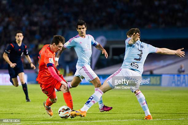 Lionel Messi of FC Barcelona competes for the ball with Andreu Fontas of Celta Vigo during the La Liga match between Celta Vigo and FC Barcelona at...