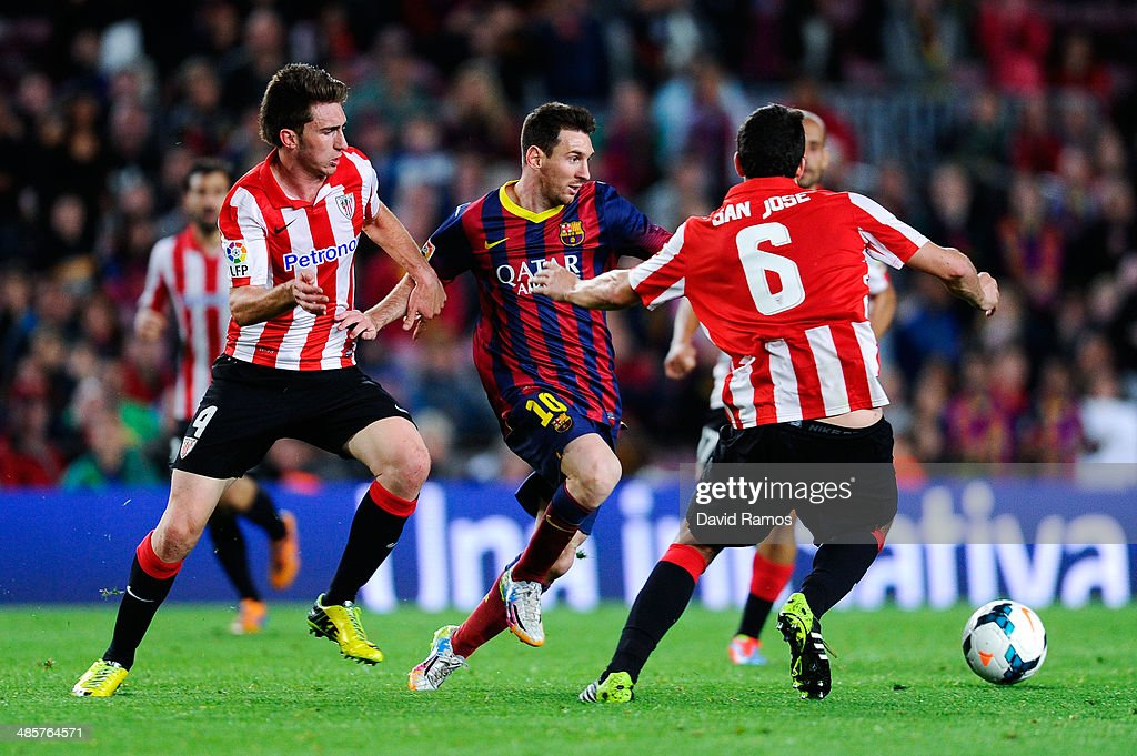 Lionel Messi of FC Barcelona competes for the ball with Aymeric Laporte and Mikel San Jose of Athletic Club during the La Liga match between FC...