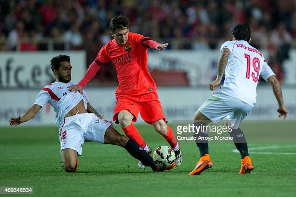 Lionel Messi of FC Barcelona competes for the ball with Benooit Tremoulinas of Sevilla FC and his teammate Ever Banega during the La Liga match...
