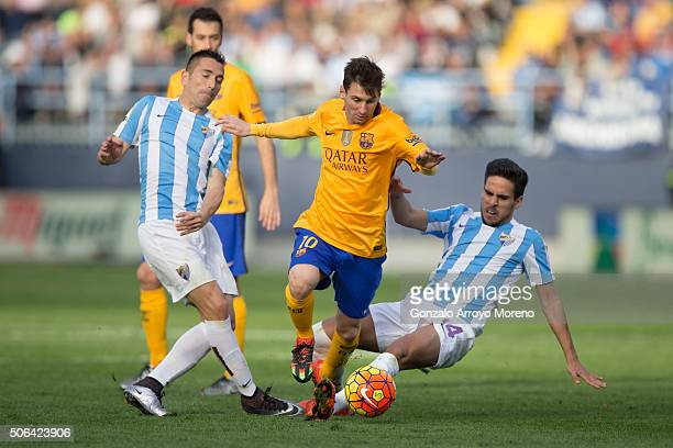 Lionel Messi of FC Barcelona competes for the ball with Charles Dias de Oliveira of Malaga CF and his teammate Jose Luis Garcia alias Recio during...