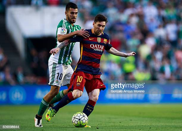 Lionel Messi of FC Barcelona competes for the ball with Dani Ceballos of Real Betis Balompie during the La Liga match between Real Betis Balompie and...