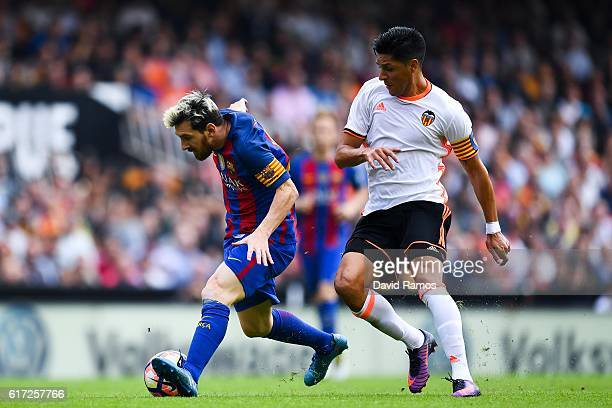 Lionel Messi of FC Barcelona competes for the ball with Enzo Perez of Valencia CF during the La Liga match between Valencia CF and FC Barcelona at...