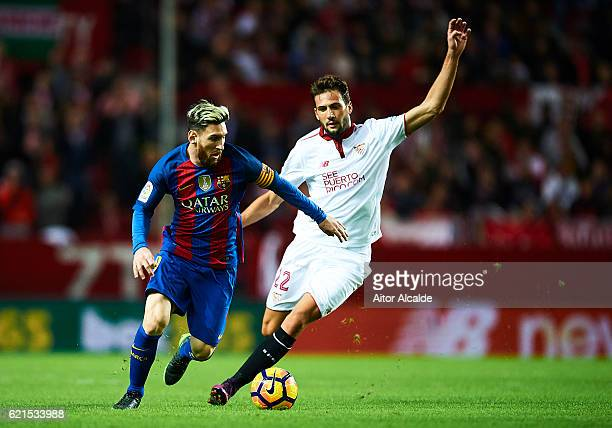 Lionel Messi of FC Barcelona competes for the ball with Franco Vazquez of Sevilla FC during the match between Sevilla FC vs FC Barcelona as part of...